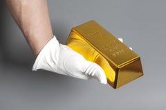 Mano del ` s degli uomini in guanti bianchi che tengono una verga d'oro fotografia stock libera da diritti