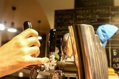 Mano del ` s dei baristi sui rubinetti della birra Immagine Stock