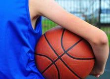 Mano del ` s del bambino che tiene la palla di pallacanestro fotografia stock libera da diritti