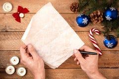 Mano del ` s del hombre del fondo de la Navidad con una pluma, llevando a cabo una letra a Fotografía de archivo