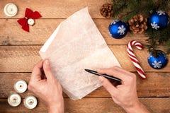Mano del ` s del hombre del fondo de la Navidad con una pluma, llevando a cabo una letra a Imagen de archivo libre de regalías