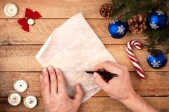 Mano del ` s del hombre del fondo de la Navidad con una pluma que escribe una letra a S Fotos de archivo libres de regalías