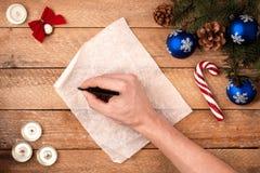 Mano del ` s del hombre del fondo de la Navidad con una pluma que escribe una letra a S Imagen de archivo libre de regalías