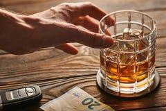 Mano del ` s del hombre que alcanza al vidrio con la bebida del alcohol y la llave del coche Concepto de la bebida y de la impuls imagenes de archivo