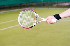 Mano del ` s del jugador de tenis que sostiene una estafa Imagen de archivo libre de regalías