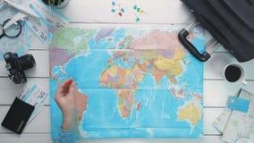 Mano del ` s del viaggiatore di vista superiore che seleziona un paese per il viaggio e messo un perno della bandiera allo scritt stock footage