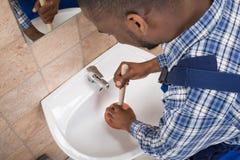Mano del ` s dell'idraulico facendo uso del tuffatore nel lavandino del bagno fotografie stock