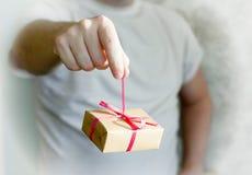 Mano del ` s dell'uomo che tiene un regalo Immagini Stock