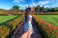 Mano del ` s dell'uomo della tenuta della donna e condurrlo a Wat Mahathat Temple nel recinto del parco storico di Sukhothai fotografia stock libera da diritti