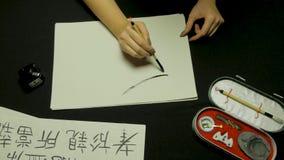 Mano del ` s della donna che scrive calligrafia cinese Mano femminile che tiene i caratteri cinesi di una spazzola di scrittura immagine stock libera da diritti