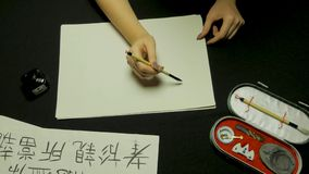 Mano del ` s della donna che scrive calligrafia cinese Mano femminile che tiene i caratteri cinesi di una spazzola di scrittura fotografia stock libera da diritti