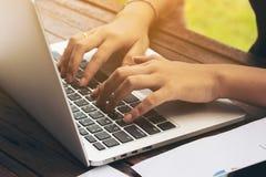 Mano del ` s della donna che scrive sul computer portatile fotografia stock