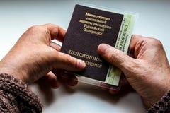Mano del ` s della donna che tiene il certificato russo di pensione fotografie stock libere da diritti