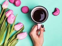 Mano del ` s della donna che tiene tazza con caffè ed i tulipani rosa Fotografie Stock