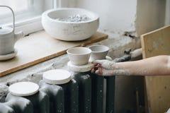 Mano del ` s della donna con la ciotola ceramica allo studio delle terraglie fotografie stock