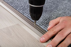 Mano del ` s della persona che installa tappeto sul pavimento immagine stock libera da diritti