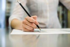 Mano del ` s della ragazza con una matita Immagini Stock Libere da Diritti