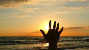 Mano del ` s della ragazza, toccante la luce solare, contro lo sfondo del tramonto del mare Ragazza felice che esamina il sole br video d archivio