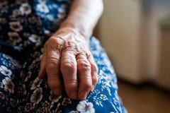 Mano del ` s della signora anziana con le grinze ed alto vicino della fede nuziale immagine stock