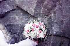 Mano del ` s della sposa con il mazzo, parete di pietra Fotografia Stock