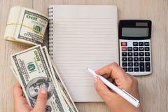 Mano del ` s delle donne con la penna, il taccuino vuoto, i dollari di banconote ed il calcolatore su fondo di legno leggero Fotografia Stock