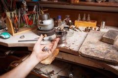 Mano del ` s del gioielliere del primo piano che lavora ad un anello sul fondo dell'officina Anello che ripara concetto Fotografia Stock