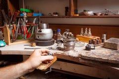 Mano del ` s del gioielliere del primo piano che lavora ad un anello sul fondo dell'officina Anello che ripara concetto Immagini Stock Libere da Diritti