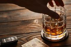 Mano del ` s del hombre que alcanza al vidrio con la bebida del alcohol y la llave del coche Concepto de la bebida y de la impuls fotos de archivo