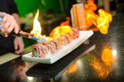 Mano del ` s del hombre que sostiene la hornilla de la antorcha El cocinero prepara el sushi foto de archivo libre de regalías