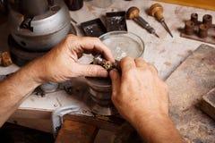 Mano del ` s del joyero del primer que trabaja en un anillo en fondo del taller Anillo que repara concepto foto de archivo