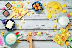 Mano del ` s del niño con las galletas y los ingredientes de Sugar Easter para el bakin Fotos de archivo libres de regalías