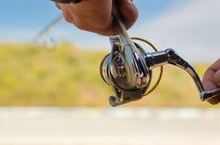 Mano del ` s del pescador con la caña de pescar foto de archivo