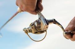 Mano del ` s del pescador con una caña de pescar en un fondo azul fotografía de archivo libre de regalías