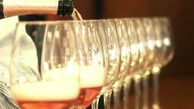 Mano del Sommelier que vierte el vino rojo en una fila de cristales almacen de video