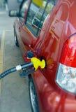 Mano del surtidor de gasolina en un coche Imagenes de archivo