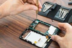 Mano del técnico que repara el teléfono móvil foto de archivo