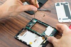 Mano del técnico que repara el teléfono móvil fotos de archivo libres de regalías