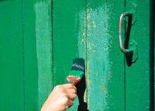 Mano del trabajador con el cepillo que pinta la puerta de madera Foto de archivo libre de regalías