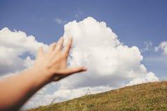 Mano del viaggiatore che raggiunge fuori alle montagne ed alle nuvole del cielo Fuoco sopra immagini stock libere da diritti