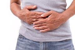 Mano del viejo hombre que sostiene el estómago que sufre del dolor, diarrea, i Foto de archivo