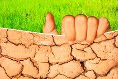 Mano dell'adolescente che tiene suolo incrinato durante il bus di periodo di siccità Fotografia Stock