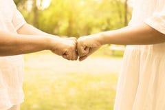 Mano dell'anziano asiatico della donna che d? l'urto del pugno alle giovani donne delle mani ad all'aperto di mattina, immagine p immagini stock