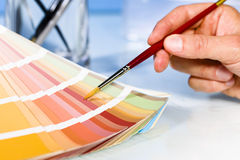 Mano dell'artista che indica i campioni di colore in tavolozza con il pennello Fotografia Stock Libera da Diritti