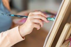 Mano dell'artista con la pittura della spazzola allo studio di arte Immagine Stock Libera da Diritti