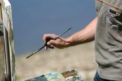 Mano dell'artista con una spazzola fotografia stock libera da diritti