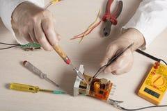 Mano dell'elettricista con la sonda del multimetro al gabinetto elettrico dell'apparecchiatura elettrica di comando Strumenti di  immagine stock