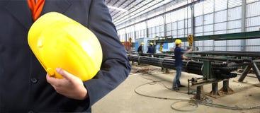 Mano dell'ingegnere che tiene casco giallo Immagine Stock