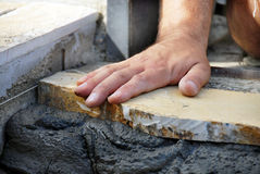 Mano dell'operaio sul flagstone Fotografia Stock Libera da Diritti