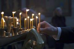 Mano dell'uomo che accende le candele in una chiesa Immagine Stock Libera da Diritti