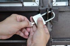Mano dell'uomo che chiude porta a chiave d'acciaio con il lucchetto Fotografia Stock